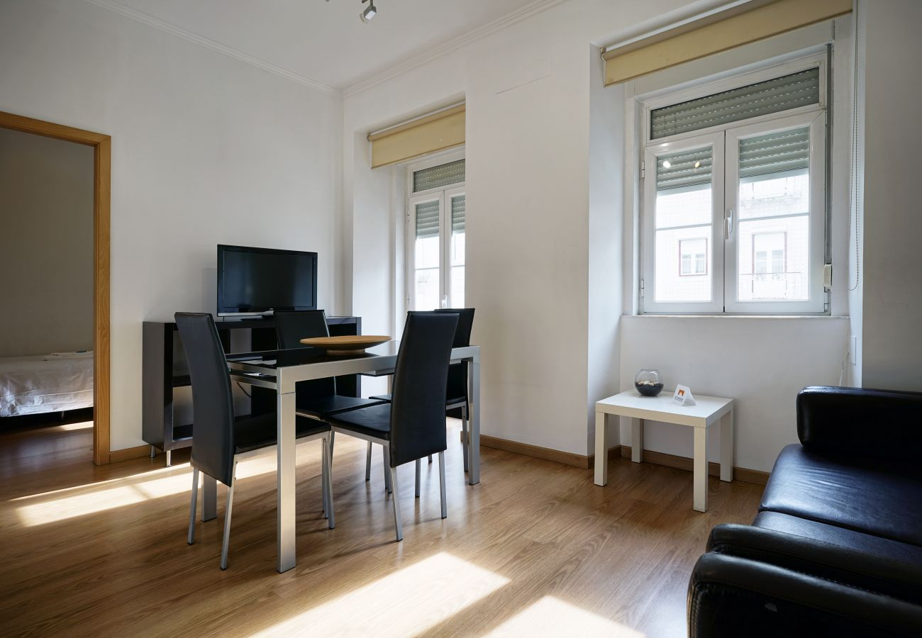 Living room with plenty of natural light, TV, dining table and sofa bed | 3 bedroom apartment Arroios Lisbon