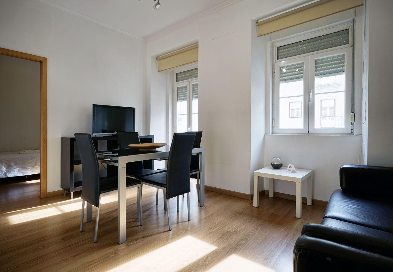 Sala de estar con mucha luz natural, TV, mesa de comedor y sofá cama | 3 dormitorios Arroios Lisboa